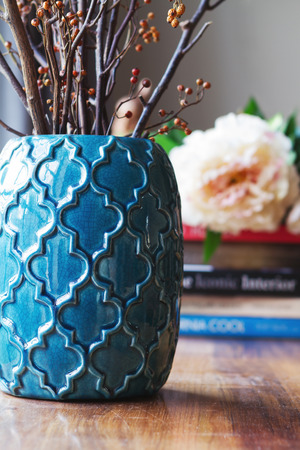 Photo for Close up of teal moroccan vase with sticks and background decor in home interior - Royalty Free Image