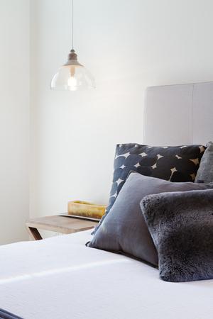 Foto de Luxury bedroom details of dark grey throw pillows and bedside penant light - Imagen libre de derechos
