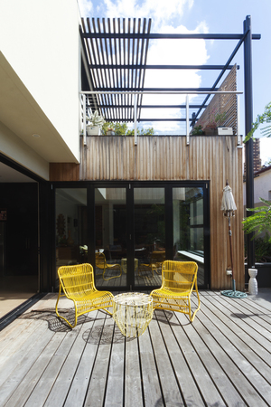 Photo for Pair of yellow cane outdoor chairs on wooden deck in contemporary courtyard - Royalty Free Image