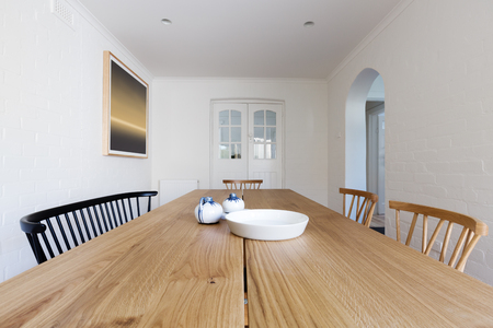 Photo for Close up of Danish styled dining room table and chairs in renovated apartment - Royalty Free Image
