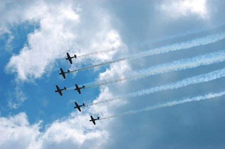 Six planes flying in formation against a cloudy blue sky