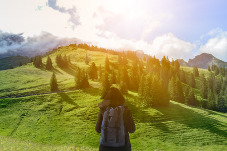 Girl has look at the big mountain and blue sky background in the morning and think how to go. Travel, Adventure and Recreation concept.