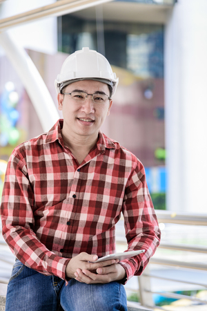 Asian business and engineer man with red scott shirt has planning and working for design buiding and city.