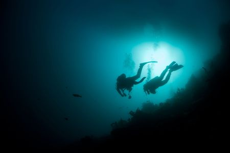Two scuba divers hoover in open ocean against the bright sun