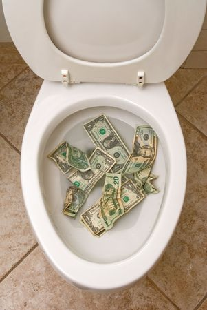 A pile of money getting ready to be flushed down the toilet.