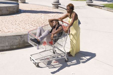 A woman pushes her passed out husband down a walkway in a shopping cart.  Can be used for partying inferences or alcohol inferences.