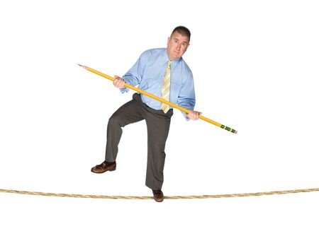 A businessman balancing on a tightrope using a giant pencil as a balancing pole.  Image is good for business risk and success inferences.