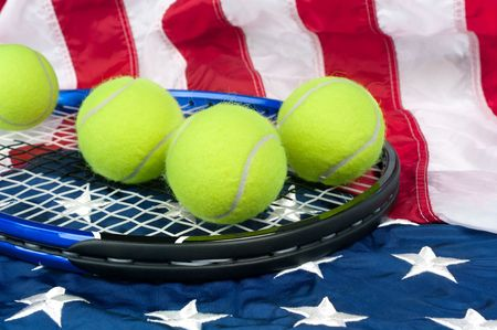 A tennis raquete with new tennis balls on an American flag