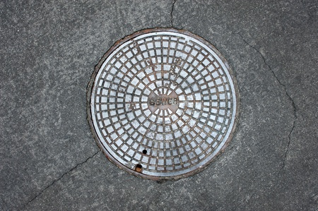 An old sewer manhole coversurrounded by an asphalt street