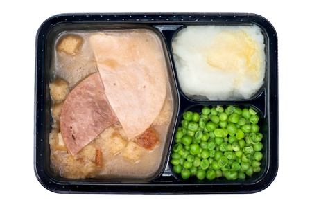 A TV dinner consisting of turkey, ham, peas and mashed potatoes isolated on white