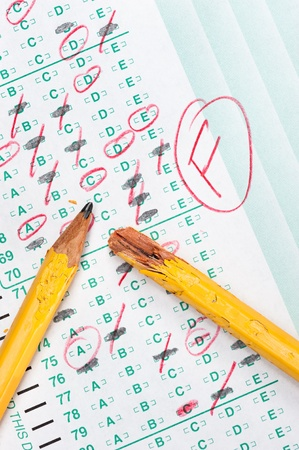 A graded test form with red scoring pencil marks indicates frustration and failure in the education system.