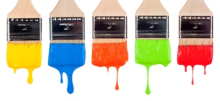 An assortment of paint brushes with dripping, wet paint of varying bright colors.