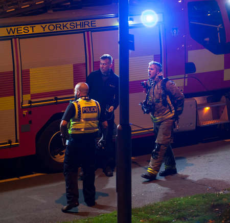 Foto für UK police officer liasing with the fire brigade at a emergency scene.A police car and a fire engine can be seen. - Lizenzfreies Bild