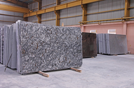 Various shades of Indian polished natural granite floor slabs kept in stacks in storehouse