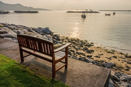 Wooden bench for relaxation at waterfront of Khlong Wan beach, Thailand