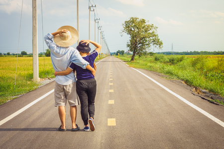 Romantic young Asian couple embracing on countryside road. They are tourist and traveling in Thailand, Southeast Asia.