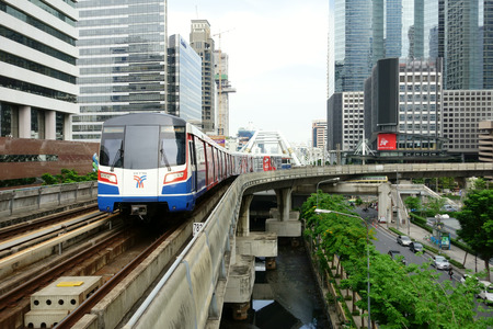 BANGKOK - JUN 4: A BTS Skytrain on speeds along elevated rails above a city centre road on June 4, 2016 in Bangkok, Thailand. Each train of the mass transport rail network can carry 1,000 passengers.