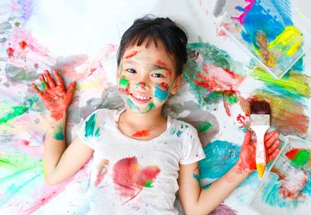 Photo pour Little girl naughty with colorful paint - image libre de droit