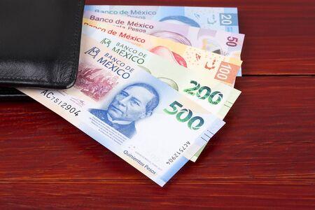 Photo pour Mexican peso in the black wallet - image libre de droit