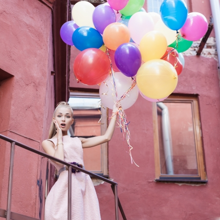Foto für young woman with colorful balloons surprised on a street - outdoors - Lizenzfreies Bild