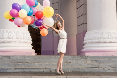Foto de Young woman with colorful latex balloons keeping her dress, urban scene, outdoors - Imagen libre de derechos
