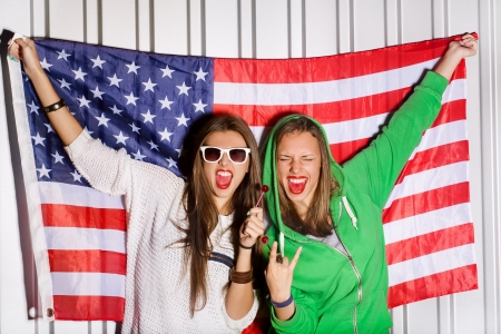 two beautiful young women holding national usa flag in background, sucking a lollipop, outdoors