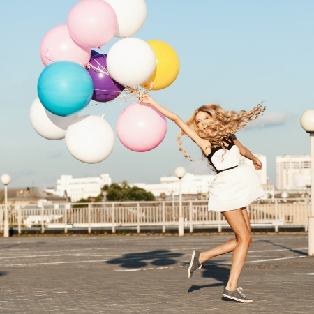 Happy young woman having fun with colorful latex balloons.  Gorgeous thick wavy hair. Outdoors, lifestyle