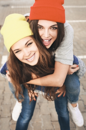 Photo pour Two young hipster girl friends together having fun. Outdoors, lifestyle. - image libre de droit