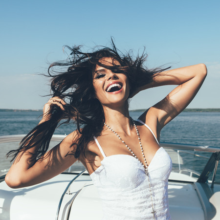 Photo pour Young happy woman have fun on the luxury boat in open sea in summer. Caucasian female model - image libre de droit