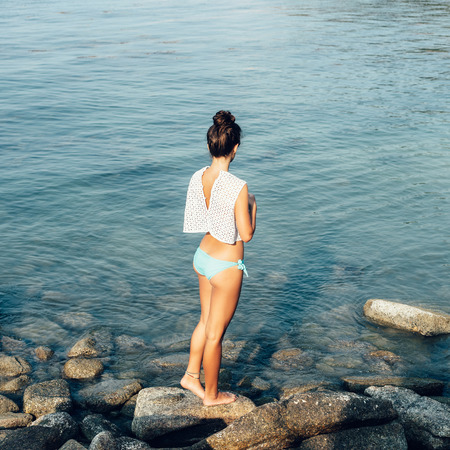 Photo pour Girl standing on coastal sea rocks. Well being healthy lifestyle - image libre de droit