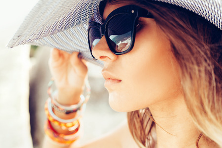 Photo pour Closeup of face of young summer sexy woman wearing hat  and sunglasses. Outdoors lifestyle portrait - image libre de droit