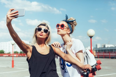 two young women taking selfie with mobile phoneの写真素材