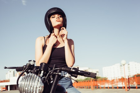 Biker girl sits on vintage custom motorcycle and buttons helmet. Outdoor lifestyle portrait