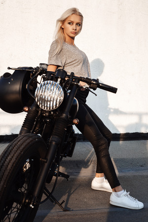 Sexy fashion female biker girl. Young woman sitting on vintage custom motorbike and looking at camera. Outdoors lifestyle portrait