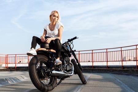 Portrait of female model Biker sitting on vintage custom motorcycle. Outdoor lifestyle portrait