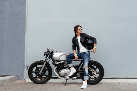 Photo for Outdoor lifestyle portrait of sexy biker girl sitting on a vintage custom motorcycle - Royalty Free Image