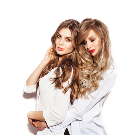 Foto de Two pretty sisters women with Healthy Long Hair ringlets wearing white shirts. Girls hugging over white background not isolated - Imagen libre de derechos