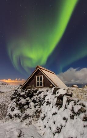 Northern lights above old cottage just outside the city of Reykjavik, Iceland
