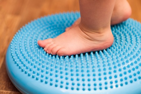 Photo pour a small child massaging his feet while standing on the rug - image libre de droit