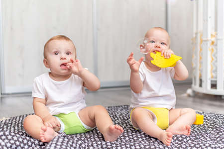 Foto de Cute happy babies play together on the floor with toys and take them in their mouths - Imagen libre de derechos