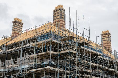 Photo pour Scaffolding creates a safe work environment at this old building which is having a new roof fitted. - image libre de droit