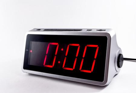 A retro looking silver digital alarm clock at midnight in red lights