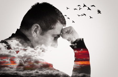 Foto de Double exposure effect of a man thinking with fist raised to forehead. Clouds cover his chest and arms as birds fly from his head. - Imagen libre de derechos
