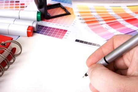 Photo pour designer surrounded by design colour swatches and pens with blank paper - image libre de droit