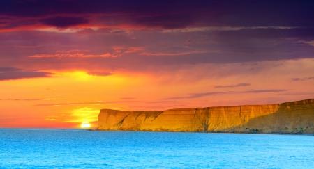 Photo pour Dramatic seascape. Summer sunset with huge cliff - image libre de droit