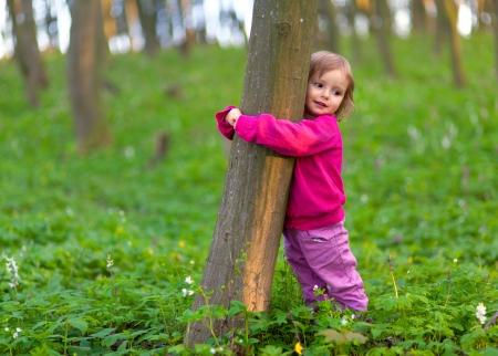 Foto de Cute little girl hugging a tree trunk in the spring forest - Imagen libre de derechos