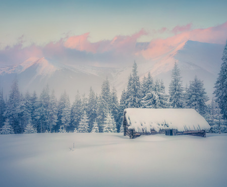 Foggy winter sunrise in mountains. Old ranch after huge snowfall. Retro style.