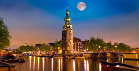 Colorful night scene with Montelbaanstoren tower on bank of the canal Oudeschans in Amsterdam, Netherlands.