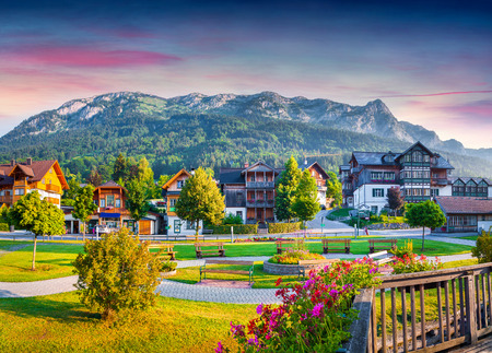 Foto de Small welcoming village Archkogl in the morning mist. Park on the near Grundlsee lake with beautiful summer flowers. Alps, Austria, Europe. - Imagen libre de derechos