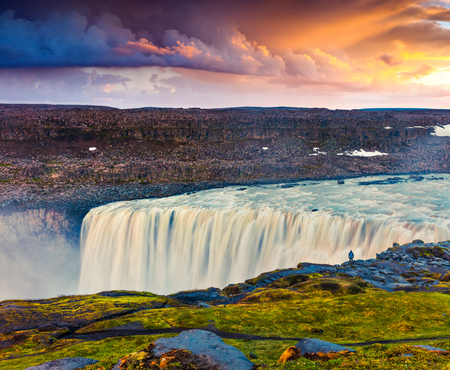 Photo pour Tourist admiring view of falling water of the most powerful waterfall in Europe - Dettifoss. Colorful summer sunrise in Jokulsargljufur National Park, Iceland. Artistic style post processed photo. - image libre de droit